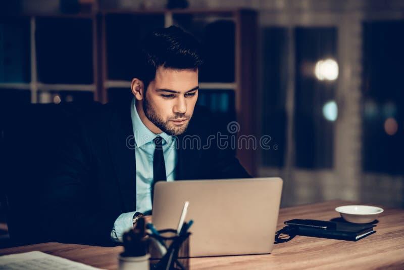 Homem de negócios focalizado Working Laptop Office na noite fotografia de stock