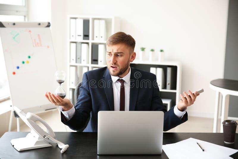 Homem de negócios forçado com a ampulheta no escritório imagem de stock royalty free