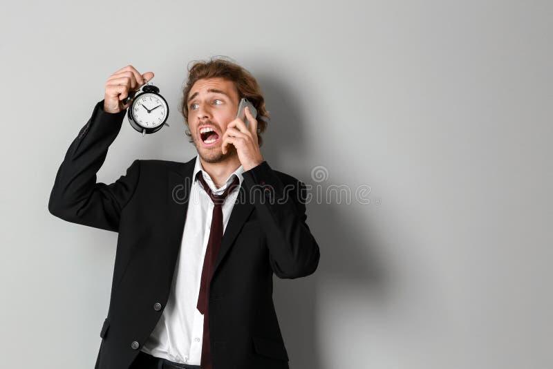 Homem de negócios forçado com despertador que fala pelo telefone celular no fundo claro imagem de stock
