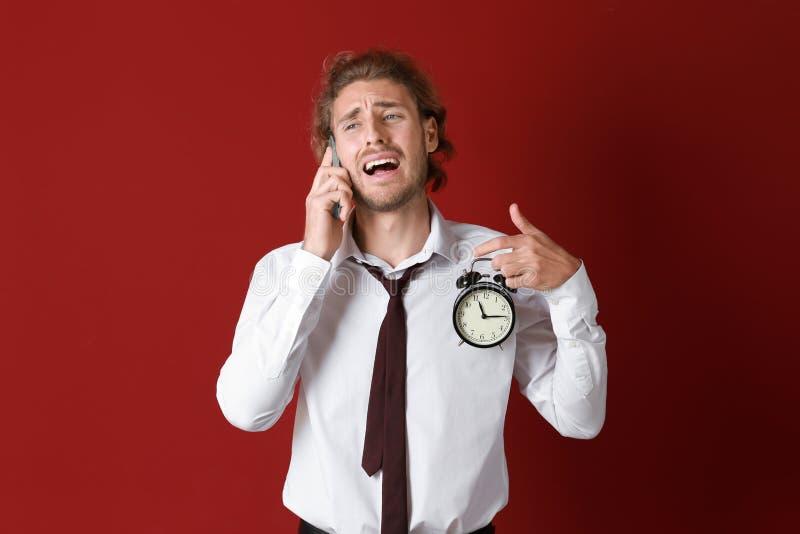 Homem de negócios forçado com despertador que fala pelo telefone celular no fundo da cor foto de stock royalty free