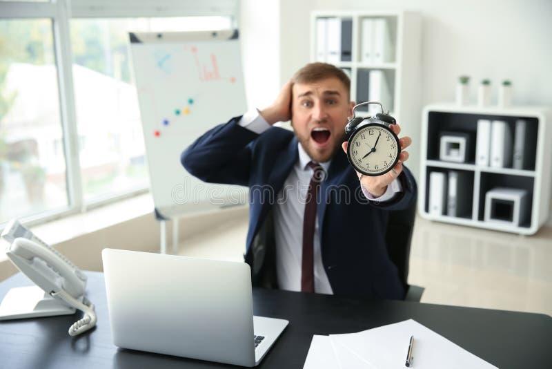 Homem de negócios forçado com o despertador no escritório imagem de stock