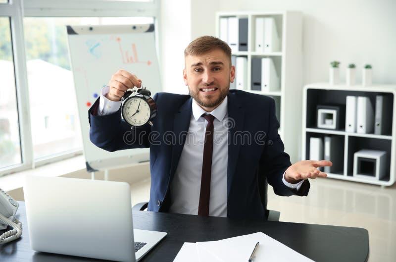 Homem de negócios forçado com o despertador no escritório foto de stock