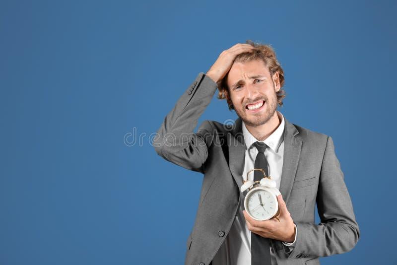 Homem de negócios forçado com o despertador no fundo azul fotos de stock royalty free