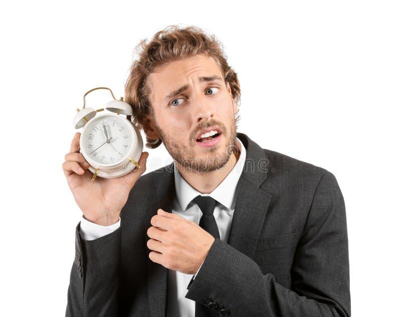 Homem de negócios forçado com o despertador no fundo branco fotos de stock royalty free