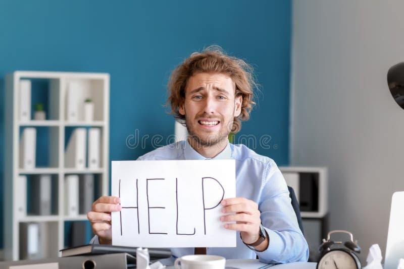 Homem de negócios forçado com palavra AJUDA escrita na folha de papel Fim do prazo no escrit?rio fotos de stock