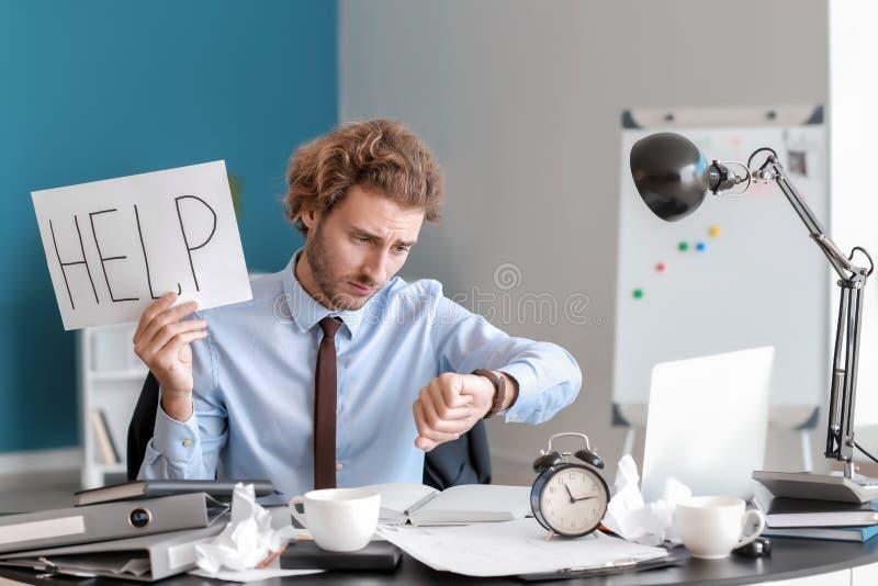 Homem de negócios forçado com palavra AJUDA escrita na folha de papel Fim do prazo no escrit?rio fotografia de stock