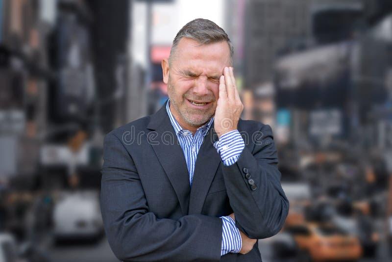 Homem de negócios forçado com sua mão a seu templo fotografia de stock