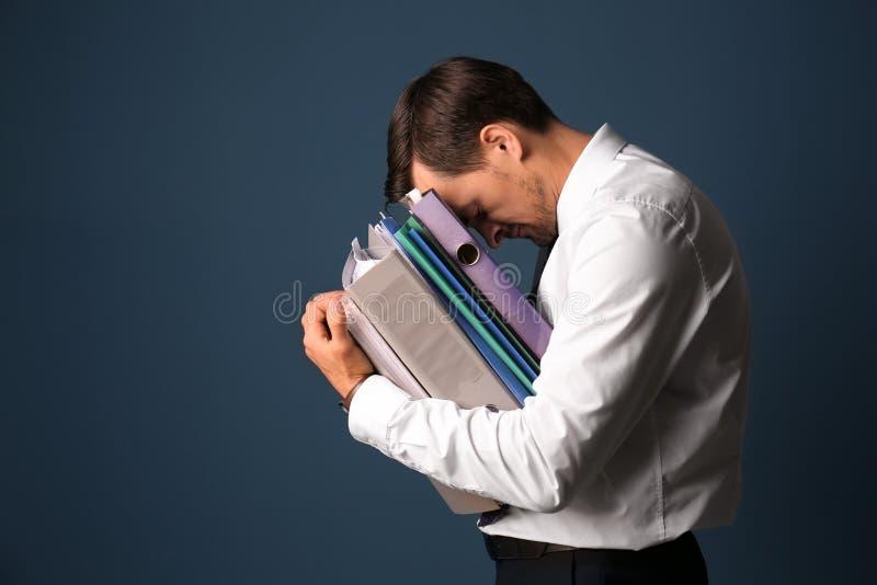 Homem de negócios forçado considerável com documentos no fundo da cor fotos de stock