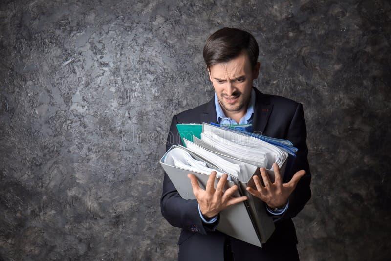 Homem de negócios forçado considerável com documentos no fundo escuro imagens de stock