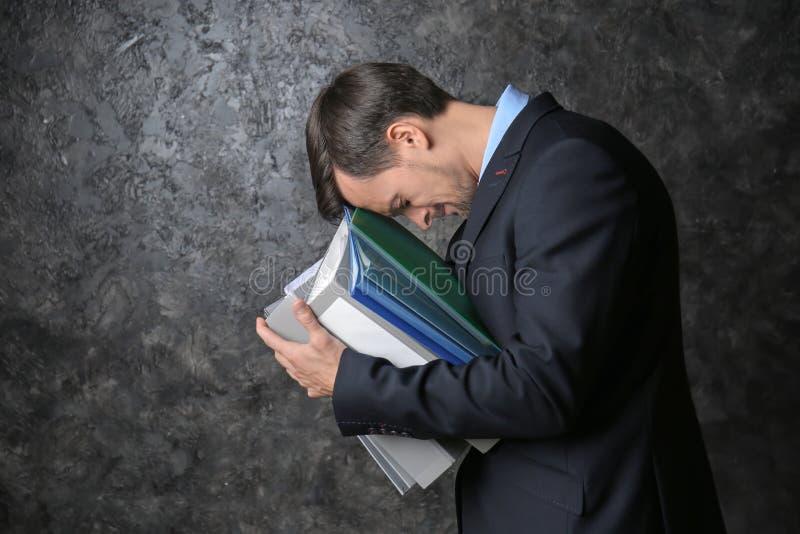 Homem de negócios forçado considerável com documentos no fundo escuro foto de stock