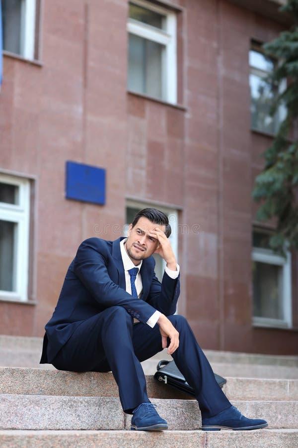 Homem de negócios forçado considerável que senta-se em escadas fora fotografia de stock