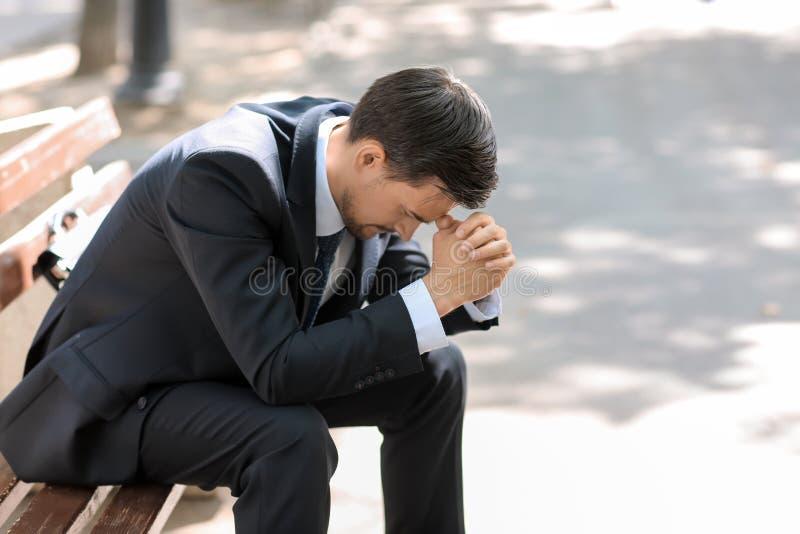 Homem de negócios forçado considerável que senta-se no banco fora imagens de stock royalty free