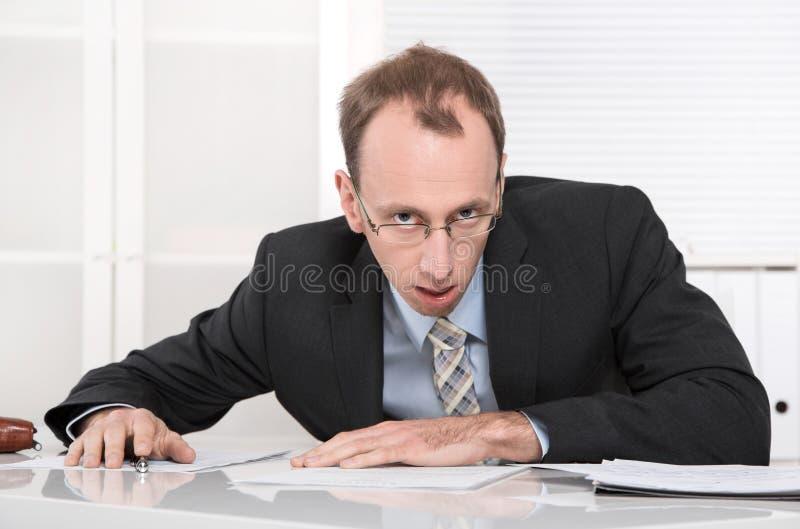Homem de negócios forçado e irritado na mesa. fotos de stock royalty free
