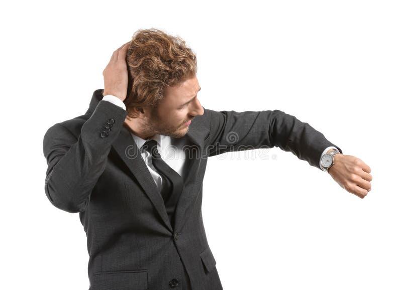 Homem de negócios forçado que olha o relógio no fundo branco fotos de stock royalty free