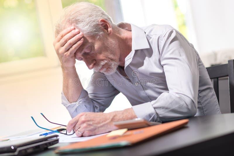 Homem de negócios forçado que senta-se no escritório, efeito da luz fotos de stock