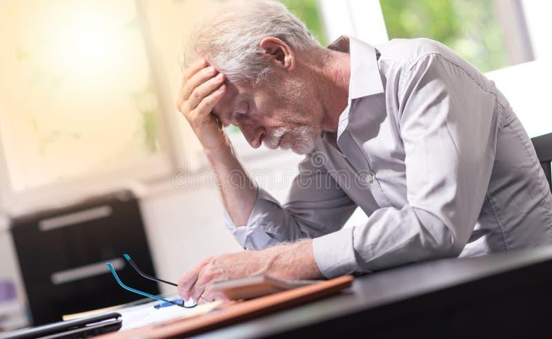 Homem de negócios forçado que senta-se no escritório, efeito da luz foto de stock royalty free