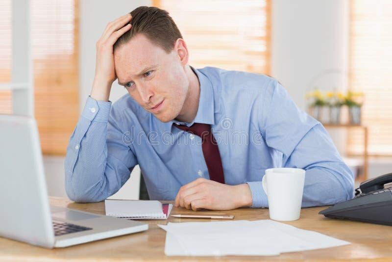 Homem de negócios forçado que trabalha em sua mesa fotografia de stock