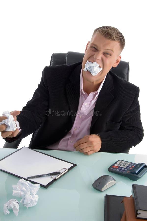 Homem de negócios frustrante com papel em sua boca foto de stock