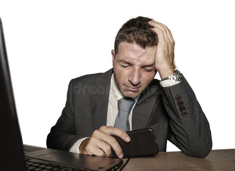 Homem de negócios frustrante e forçado novo no funcionamento do terno e do laço oprimido na mesa do laptop do escritório desesper fotos de stock royalty free