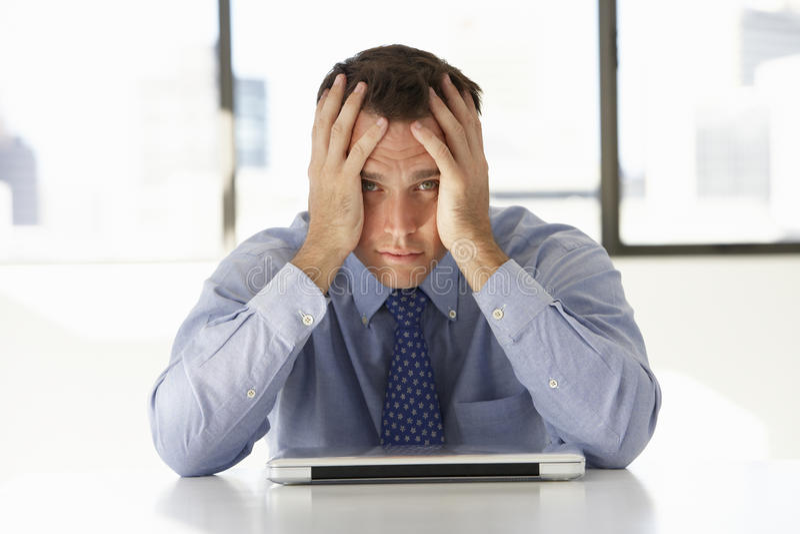 Homem de negócios frustrante Sitting At Desk no escritório usando o portátil