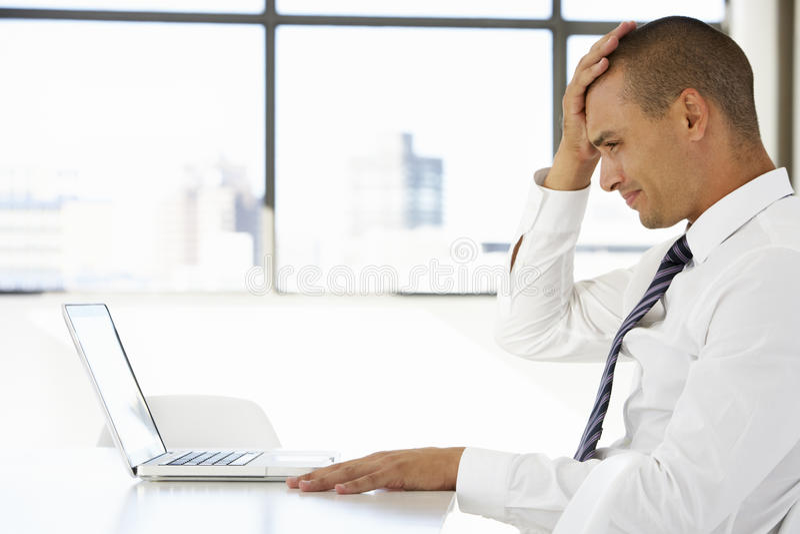 Homem de negócios frustrante Sitting At Desk no escritório usando o portátil fotos de stock