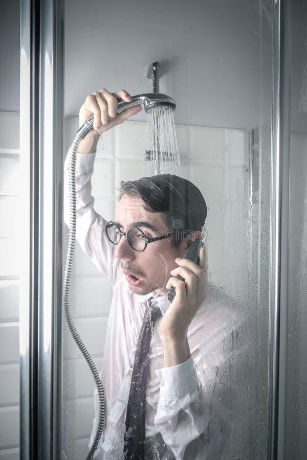 Homem de negócios furado que fala no telefone no chuveiro imagens de stock