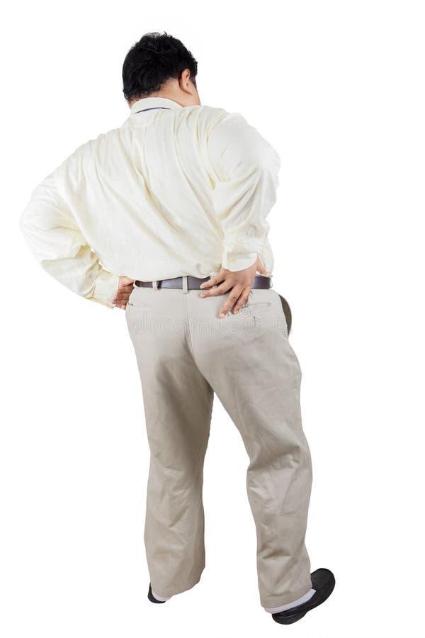 Homem de negócios gordo que tem a dor lombar no estúdio imagens de stock