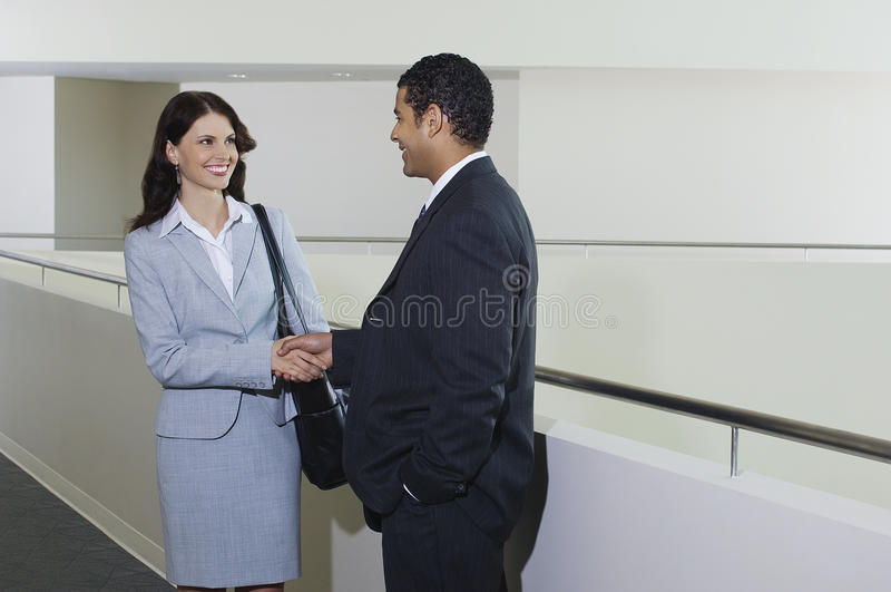 Homem de negócios Greeting Female Colleague no escritório fotografia de stock