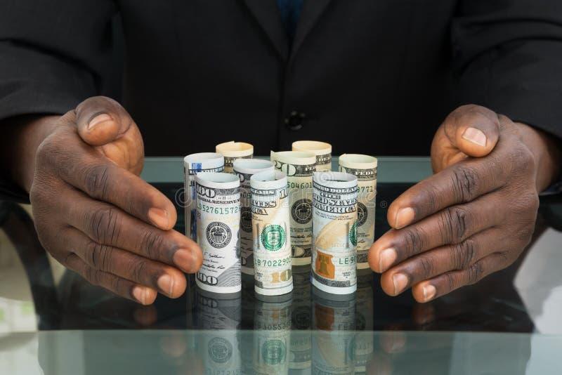 Homem de negócios Hands Protecting Banknotes fotos de stock