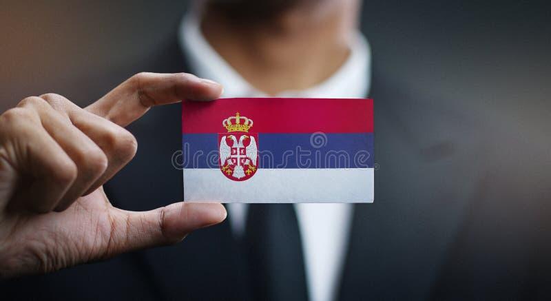 Homem de negócios Holding Card da bandeira da Sérvia imagem de stock