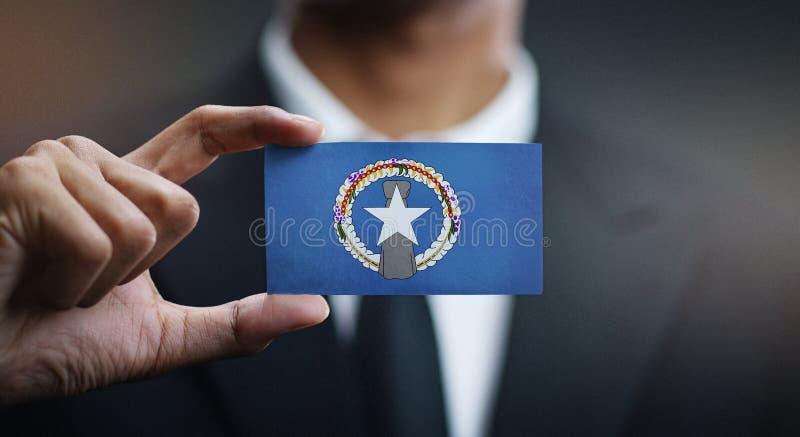 Homem de negócios Holding Card Northern Mariana Islands Flag imagem de stock royalty free