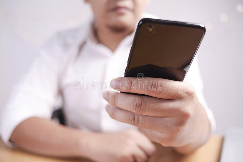 Homem de negócios Holding e utilização do telefone esperto fotografia de stock