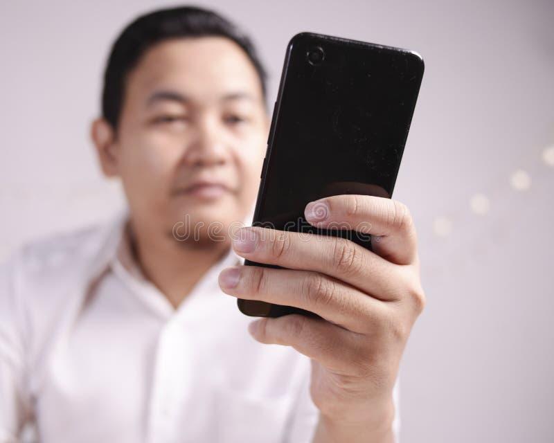 Homem de negócios Holding e utilização do telefone esperto fotos de stock