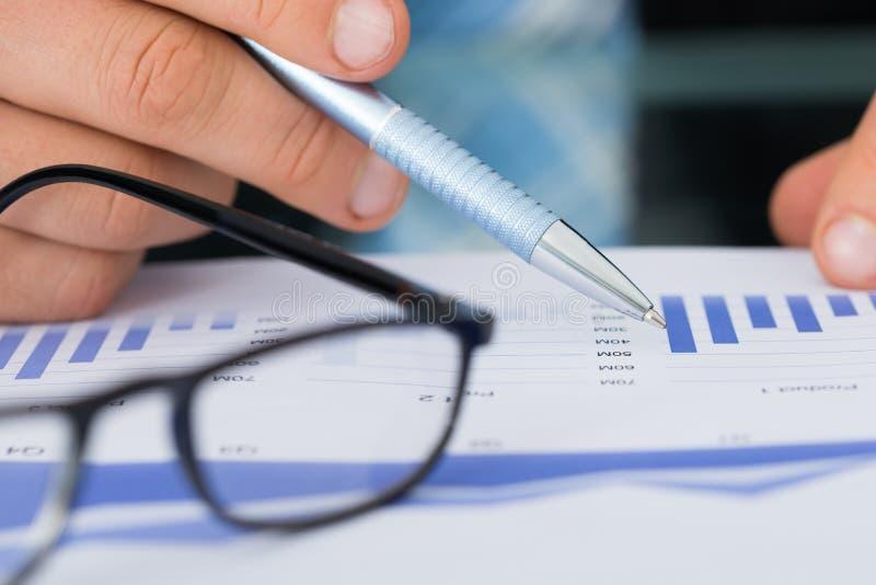 Homem de negócios Holding Pen While Analyzing Bar Graph imagem de stock royalty free
