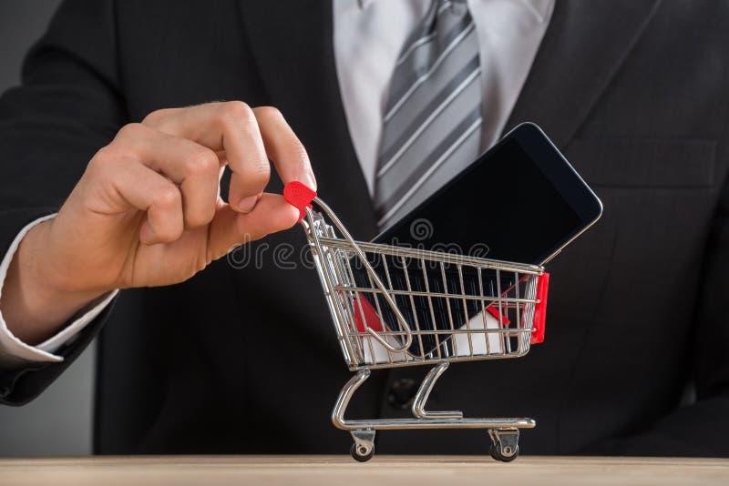 Homem de negócios Holding Shopping Trolley com telefone celular fotos de stock