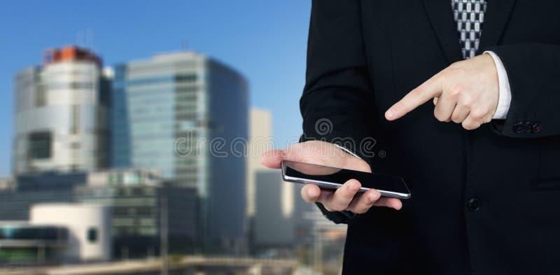 Homem de negócios Holding Smartphone disponivel e que aponta o indicador na tela dos telefones com cidade do negócio e construçõe imagem de stock