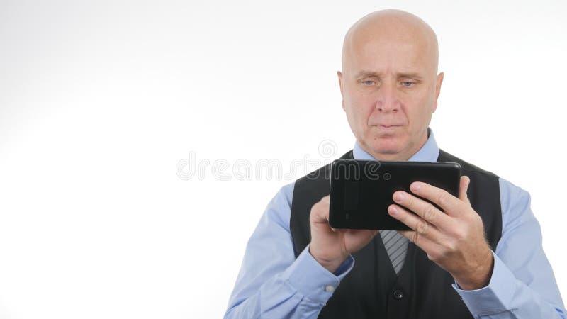Homem de negócios Image Using uma candidatura online da tabuleta de toque foto de stock