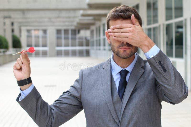 Homem de negócios impulsivo que joga dardos no espaço de escritórios fotografia de stock