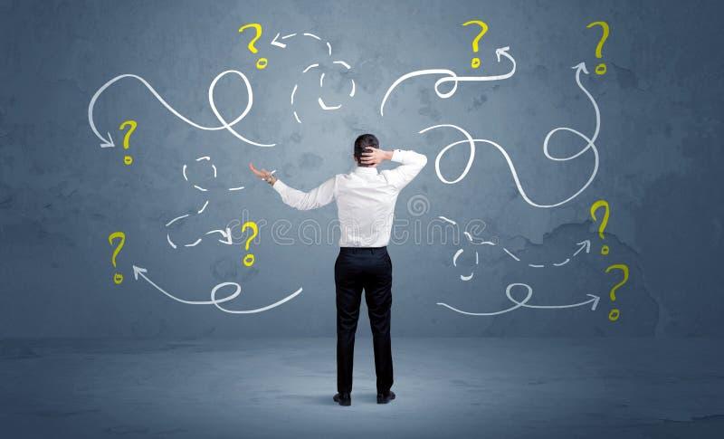 Homem de negócios incerto com pontos de interrogação fotos de stock royalty free