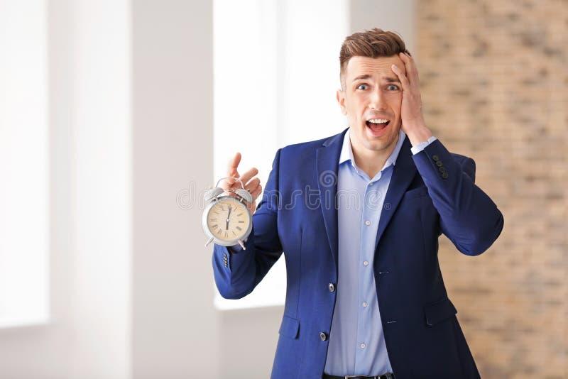 Homem de negócios incomodado com despertador dentro Conceito da gest?o de tempo fotos de stock royalty free