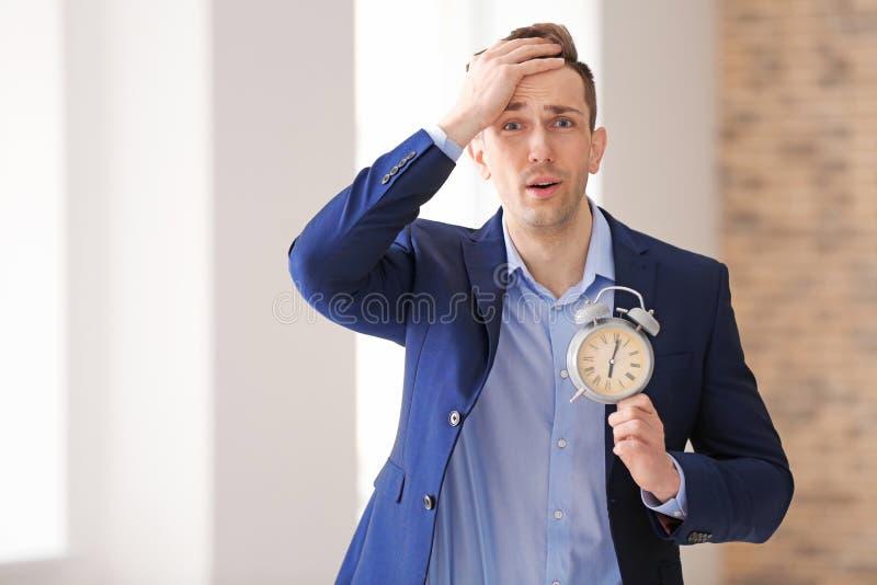 Homem de negócios incomodado com despertador dentro Conceito da gest?o de tempo foto de stock royalty free