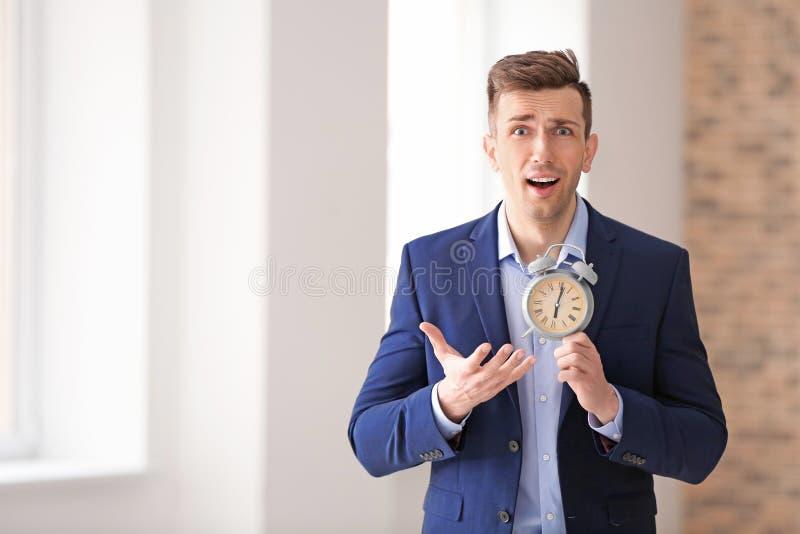 Homem de negócios incomodado com despertador dentro Conceito da gest?o de tempo fotografia de stock royalty free
