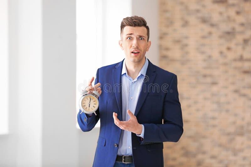 Homem de negócios incomodado com despertador dentro Conceito da gest?o de tempo imagem de stock royalty free