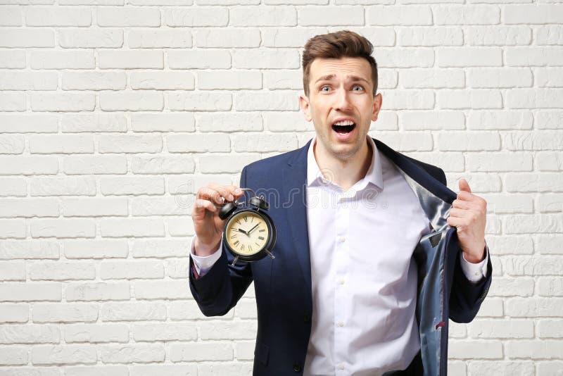 Homem de negócios incomodado com o despertador contra a parede de tijolo branca Conceito da gest?o de tempo fotografia de stock royalty free