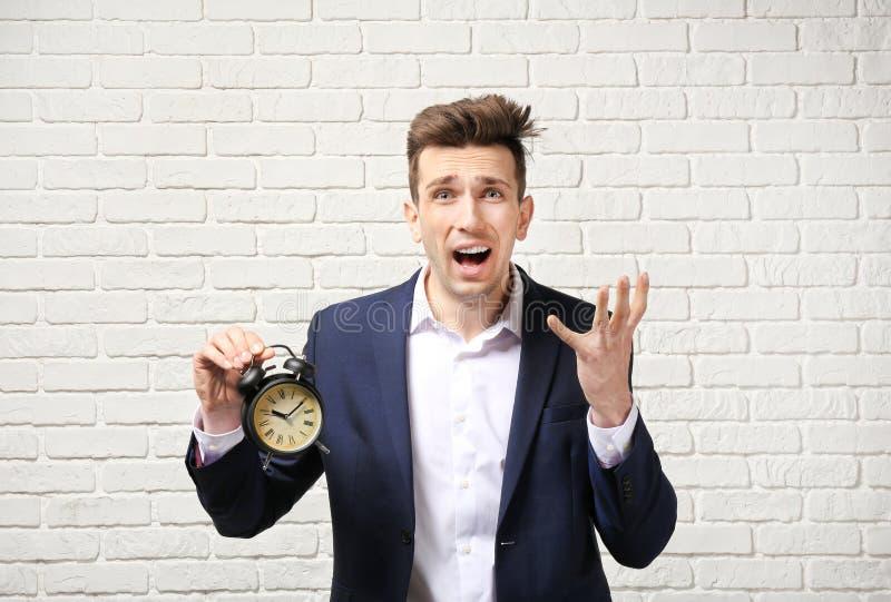 Homem de negócios incomodado com o despertador contra a parede de tijolo branca Conceito da gest?o de tempo foto de stock
