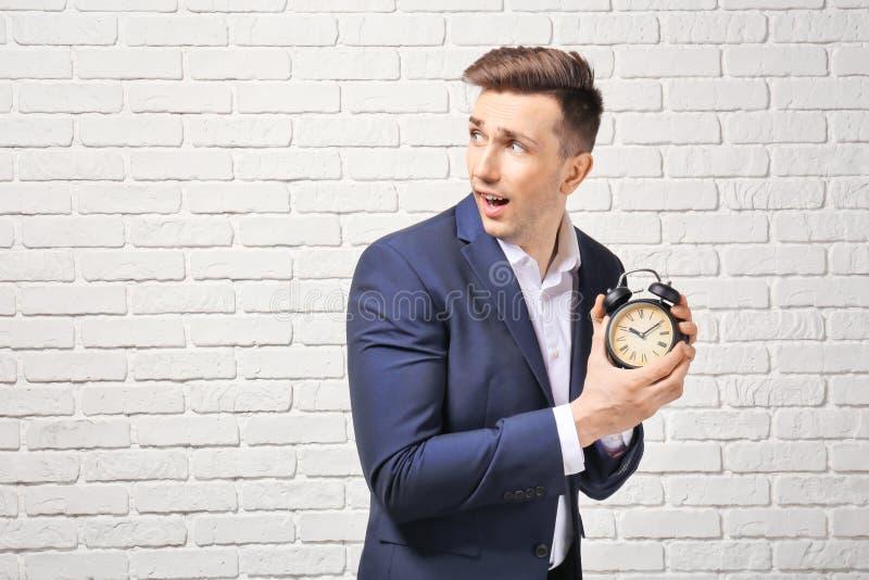 Homem de negócios incomodado com o despertador contra a parede de tijolo branca Conceito da gest?o de tempo imagem de stock