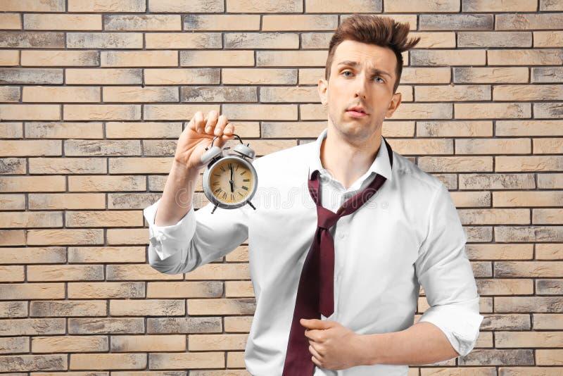 Homem de negócios incomodado com o despertador contra a parede de tijolo Conceito da gest?o de tempo imagem de stock royalty free