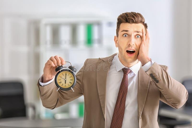 Homem de negócios incomodado com o despertador no escritório Conceito da gest?o de tempo fotografia de stock