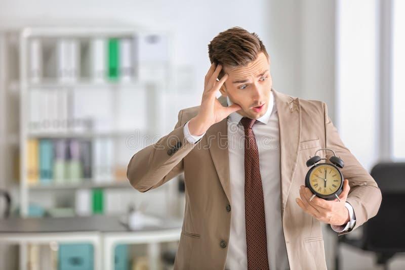 Homem de negócios incomodado com o despertador no escritório Conceito da gest?o de tempo fotos de stock