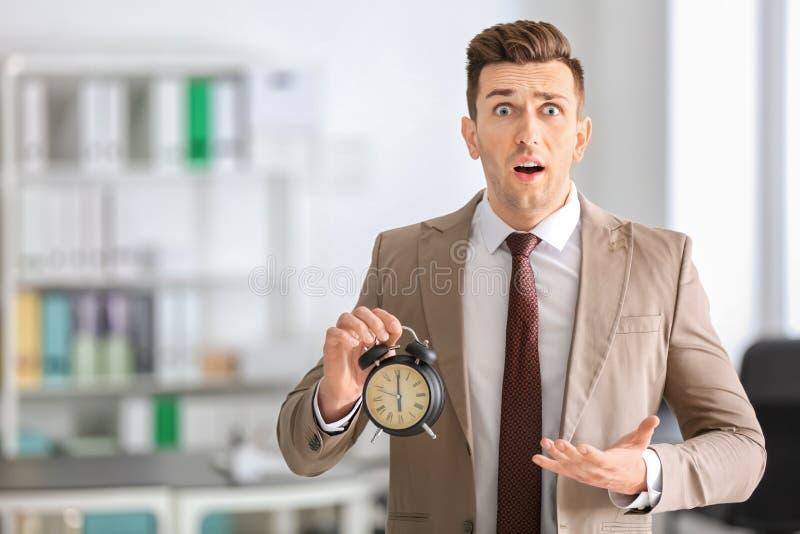 Homem de negócios incomodado com o despertador no escritório Conceito da gest?o de tempo imagens de stock